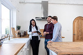 African american female real estate agent in kitchen showing gay couple around new house