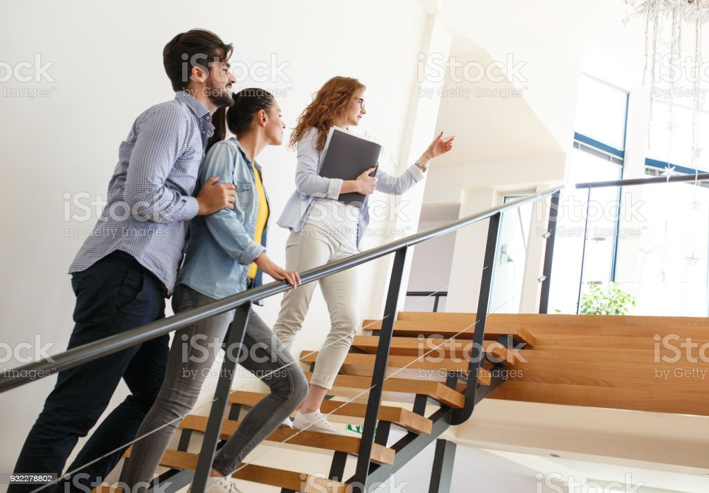 Female Real Estate agent shows interior to young couple. stock photo