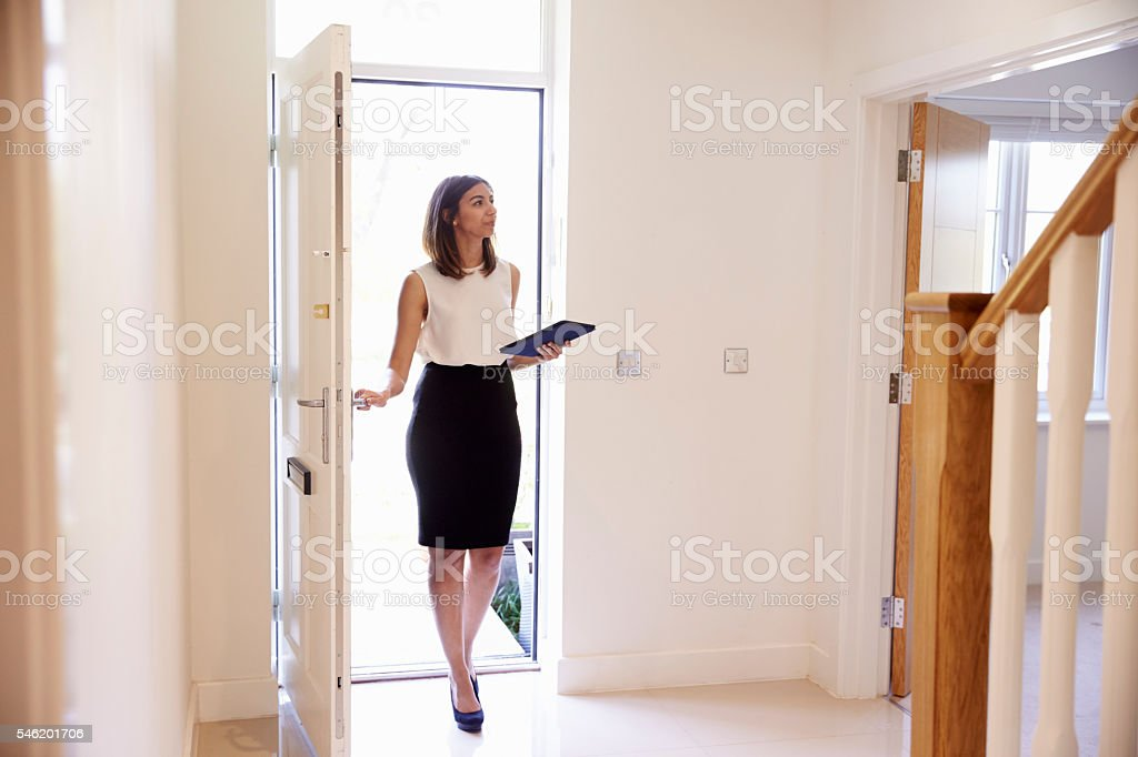 Female Realtor In Hallway Carrying Out Valuation stock photo