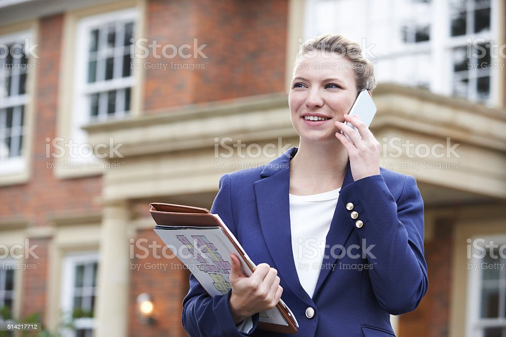 Female Realtor On Phone Outside Residential Property stock photo