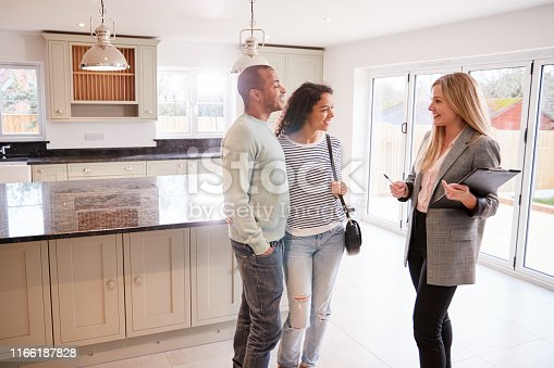 istock Female Realtor Showing Couple Interested In Buying Around House 1166187828