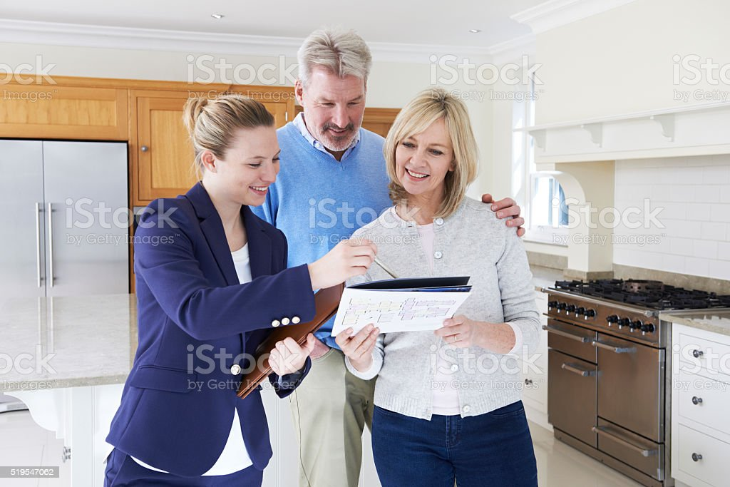 Female Realtor Showing Mature Couple Around New Home stock photo