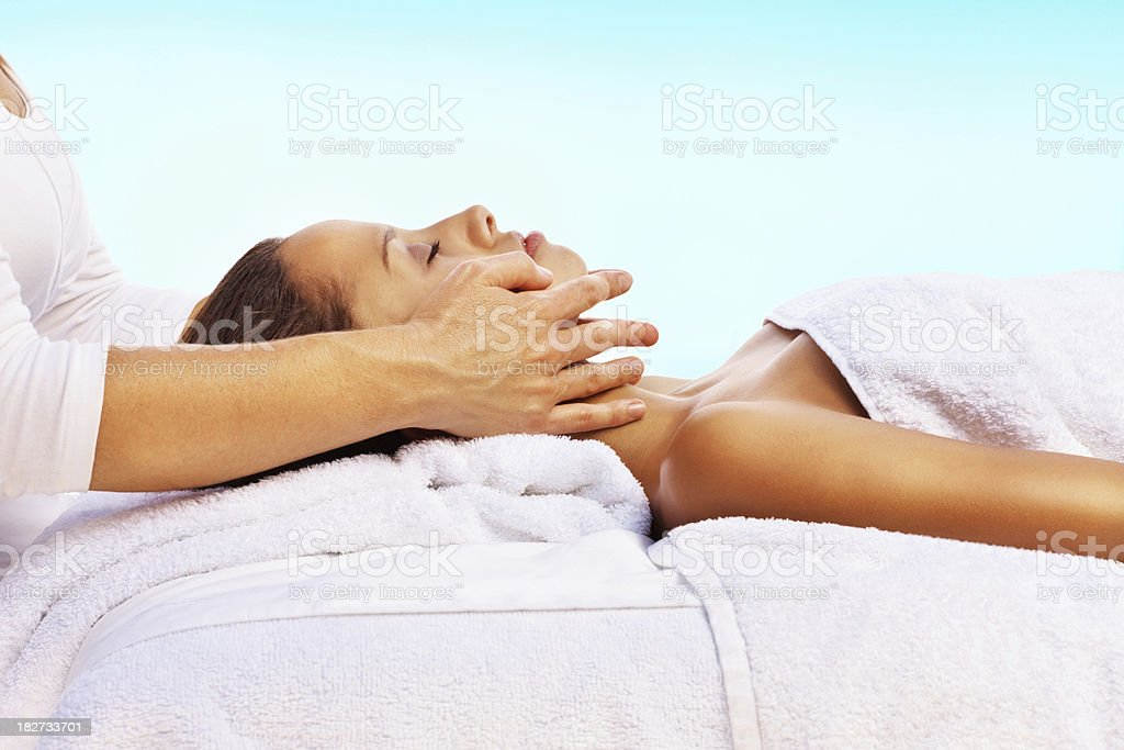 Female receiving facial massage from a masseuse royalty-free stock photo