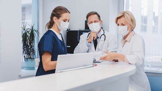 Female receptionist working at desk in clinic with doctor colleagues in medical protective masks. Epidemic prevention concept