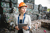Close-up of contemplative female environmental specialist in mid 30s performing onsite inspection of waste management facility.