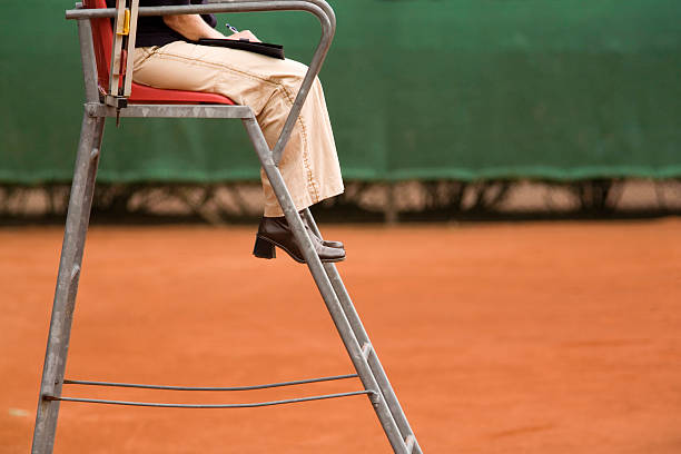 female referee on a clay tennis court female referee sitting in a chair on a clay tennis court referee stock pictures, royalty-free photos & images