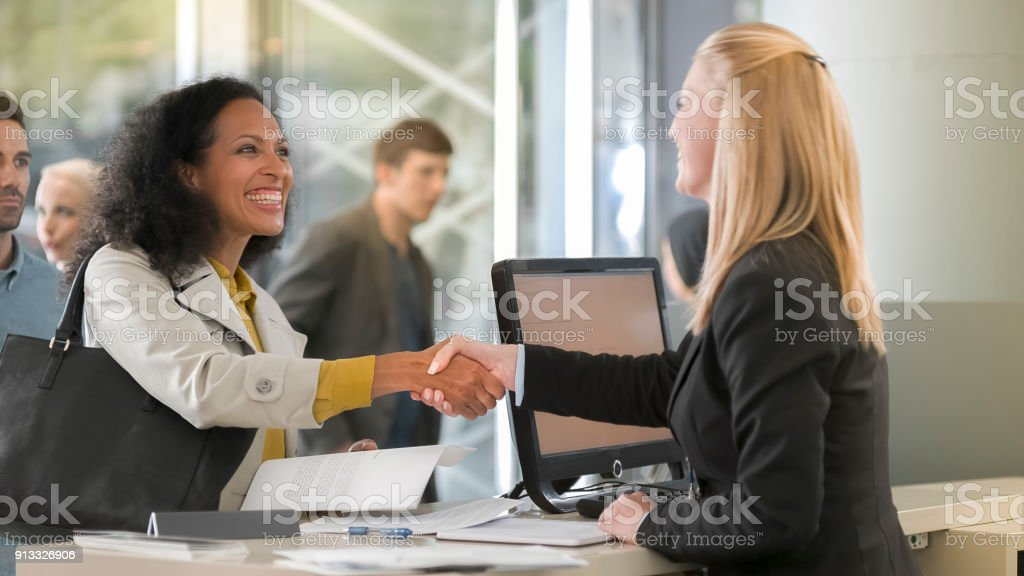 Female rental clerk giving documents to female customer renting car stock photo