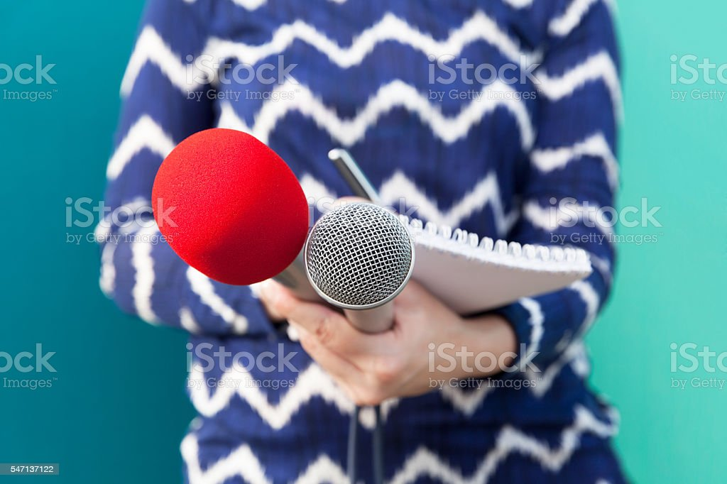 Female reporter at news conference, taking notes, holding microphones stock photo