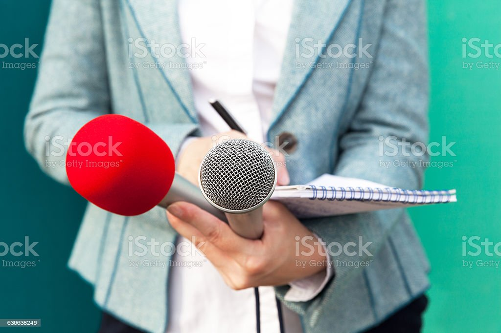 Female reporter at news conference, writing notes stock photo