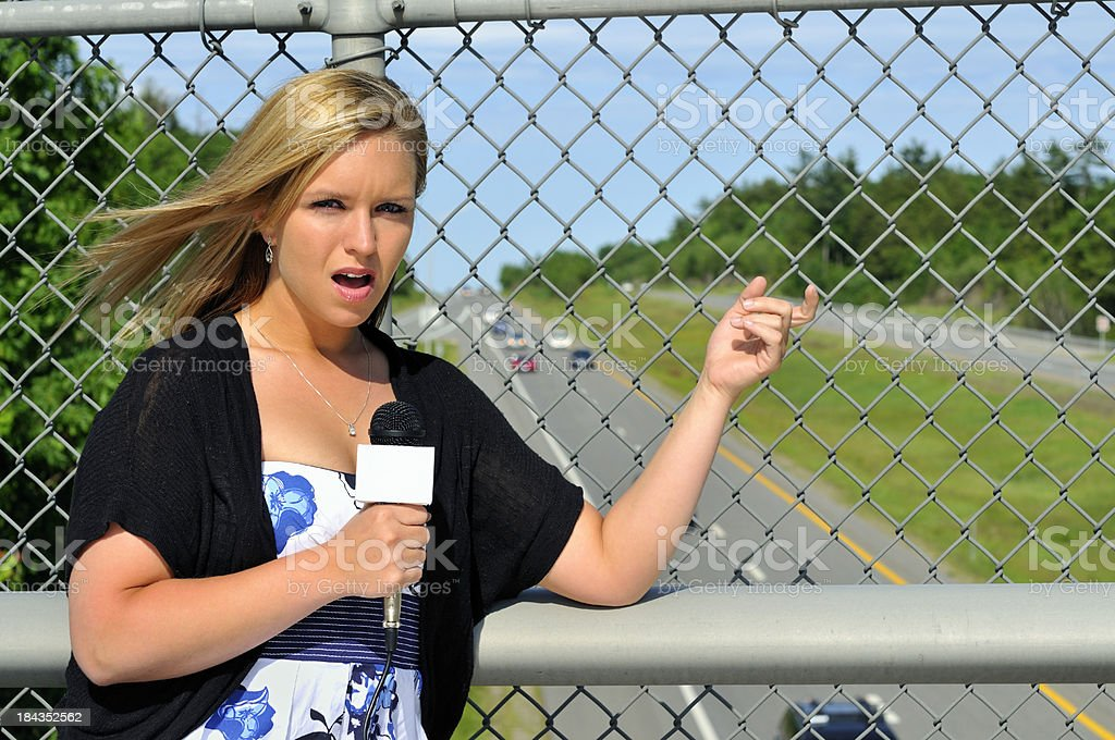 Female Reporter on Highway Overpass stock photo
