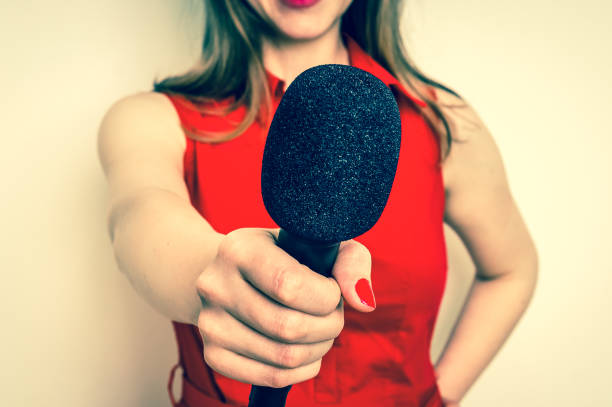Female reporter with black microphone making interview stock photo