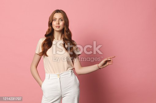 fashionable woman showing copy space left pointing isolated over pink background