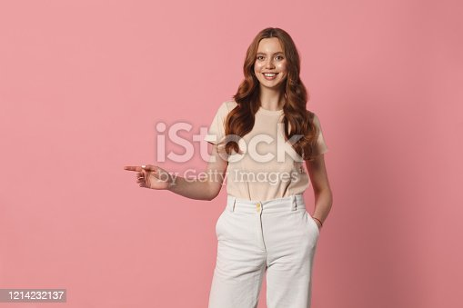 young smiling woman showing copy space left pointing isolated over pink background