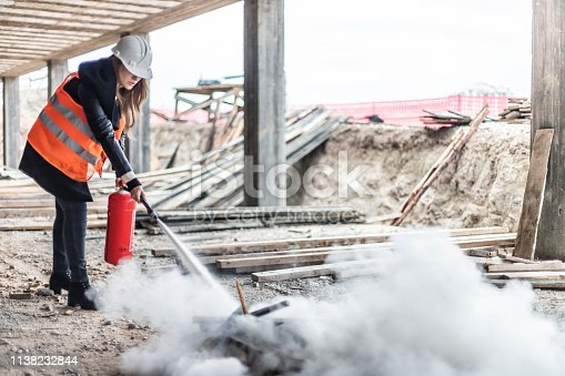 Female rescue worker with a fire extinguisher  on construction site