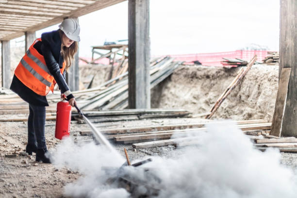 Female rescue worker with a fire extinguisher on construction site Female rescue worker with a fire extinguisher  on construction site extinguishing stock pictures, royalty-free photos & images