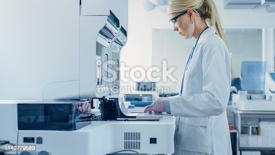 istock Female Research Scientist Putting Test Tubes with Blood Samples into Analyzer Medical Machine. Scientist Works with Modern Medical Equipment in Pharmaceutical Laboratory. 1140779589