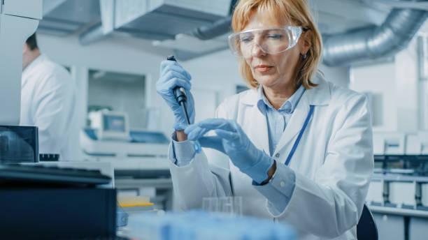 kobieta research scientist używa mikro pipety podczas pracy z probówek. ludzie w innowacyjnym laboratorium farmaceutycznym z nowoczesnym sprzętem medycznym do badań genetycznych. - laboratorium zdjęcia i obrazy z banku zdjęć