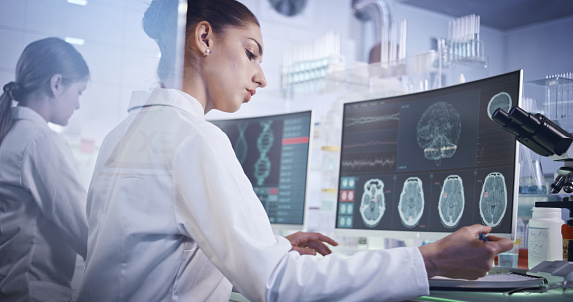 Scientists examines brainwave models in modern Neurological Research Laboratory.