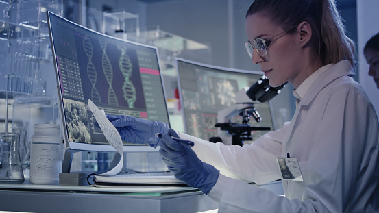 Scientists examines DNA models in modern Genetic Research Laboratory.
