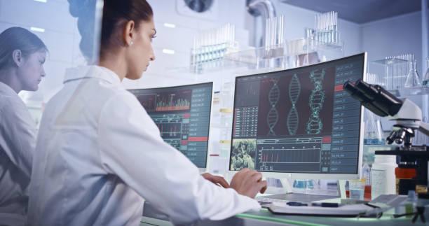 equipo de investigación femenino que estudia mutaciones en el adn. pantallas de ordenador con hélice de adn en primer plano - investigación genética fotografías e imágenes de stock