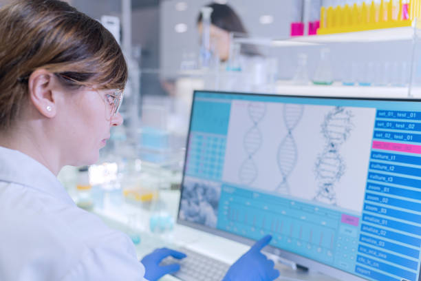 Female research team studying DNA samples. Computer screens with DNA helix in foreground stock photo