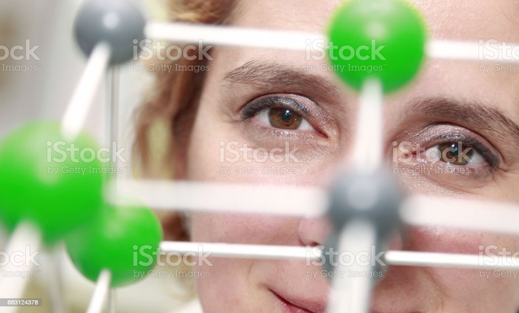Female Researcher Eyes Through a Molecular Model Structure stock photo
