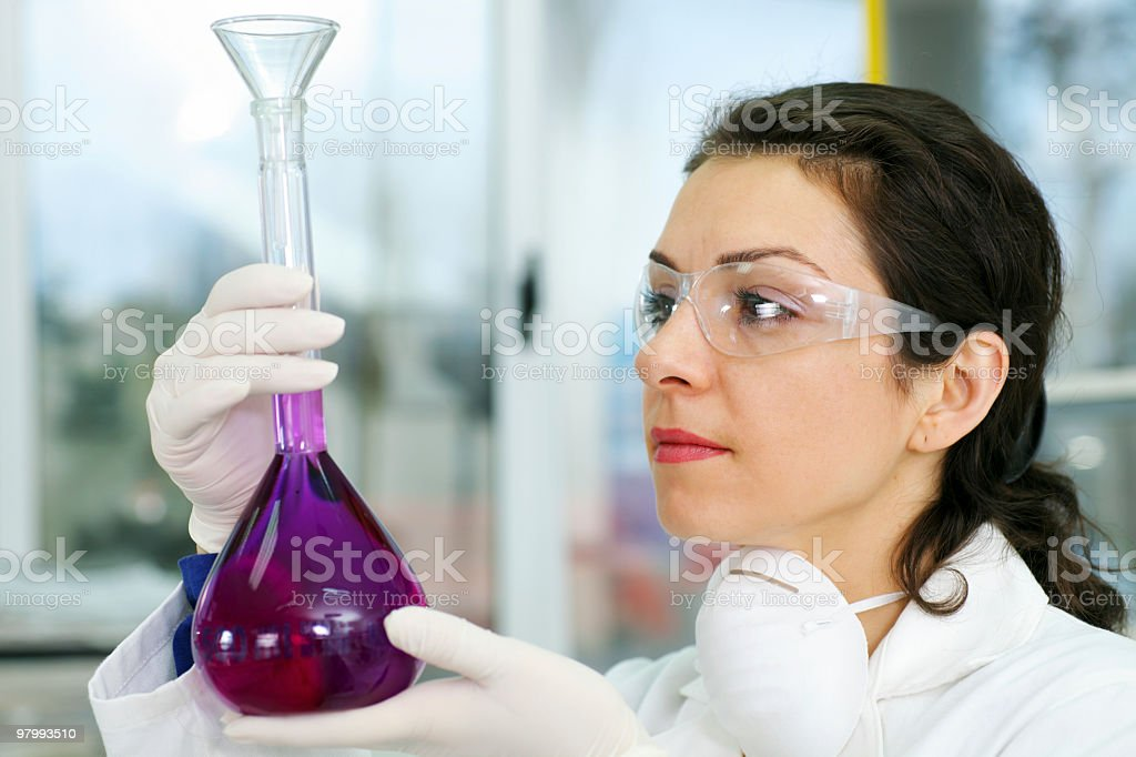 Female researcher is analyzing a magenta liquid. royalty-free stock photo