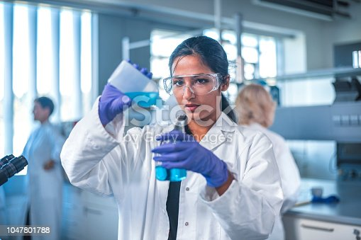 Young female researcher pouring chemical into flask. Confident scientist is doing experiment in laboratory. She is wearing protective eyewear.