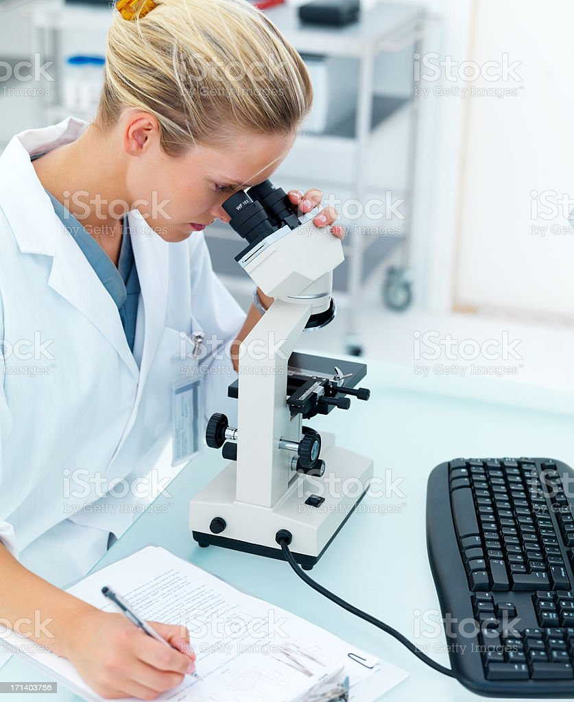 Female researcher using microscope royalty-free stock photo