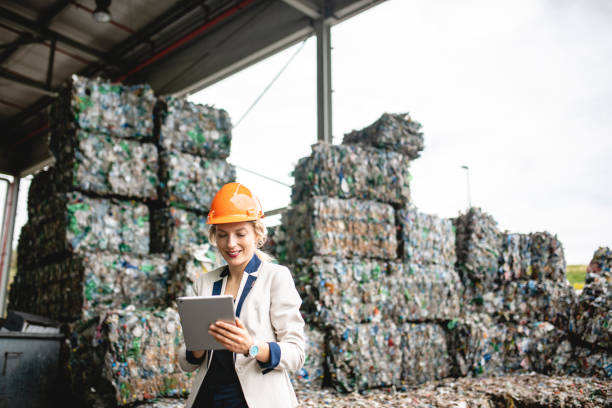 Female Resource Recovery Specialist Using Digital Tablet Close-up of female environmental expert using digital tablet for notes while conducting satisfying onsite inspection of recycling facility. social responsibility stock pictures, royalty-free photos & images
