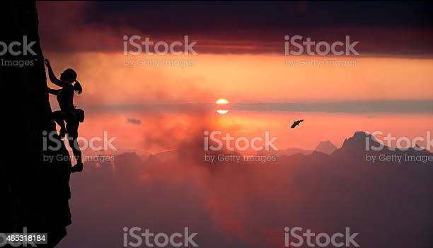 Photo of Female rock climber and mountain sunset