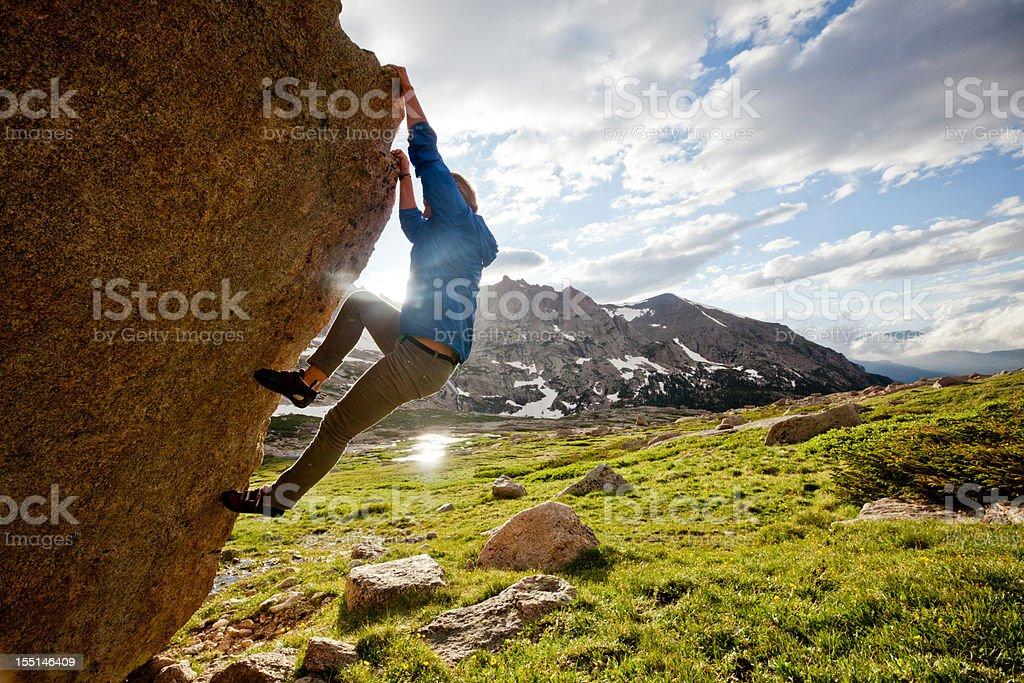 Female rock climber climbing a boulder problem royalty-free stock photo