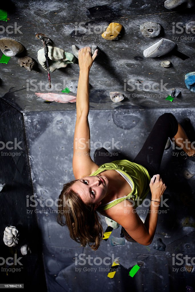 female rock climber climbing gym stock photo