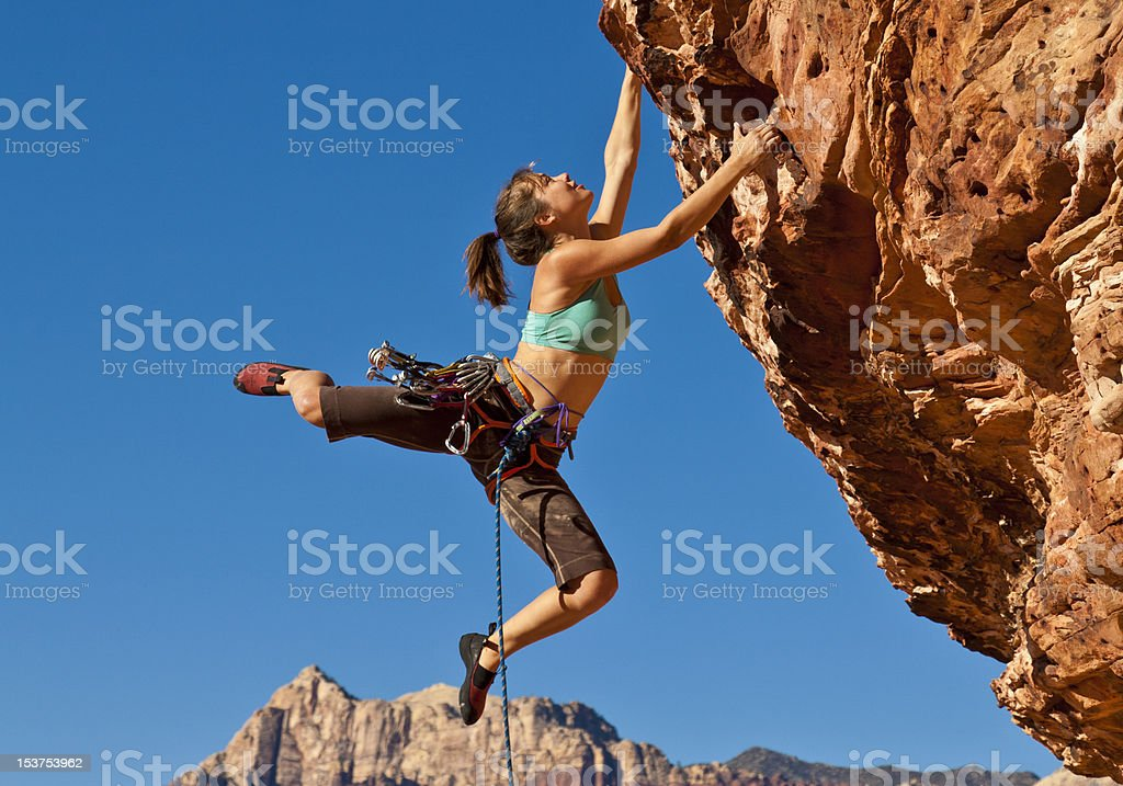 Female rock climber clinging to a cliff stock photo