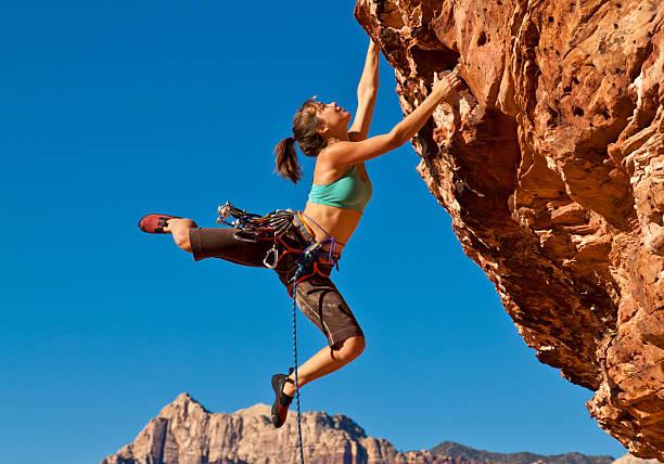 雌ロッククライマーがくっついて、崖 - ロッククライミング ストックフォトと画像