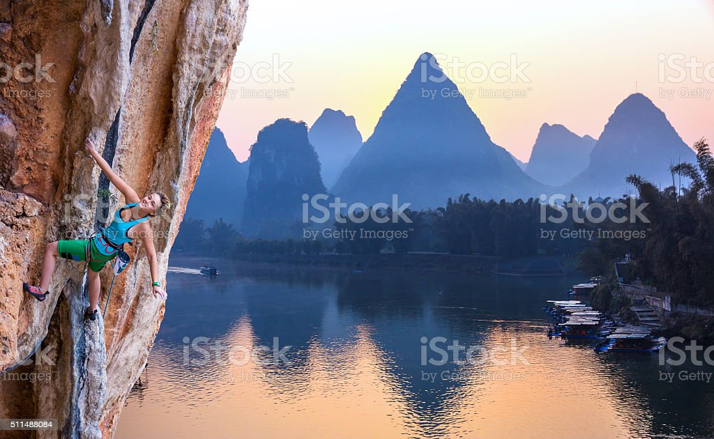 Female Rock Climber hanging on Wall in China Landscape stock photo