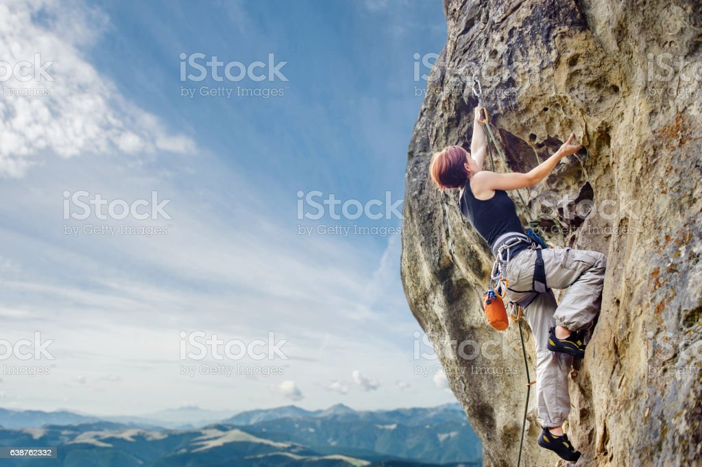 Female rock climber on steep overhanging rock cliff stock photo