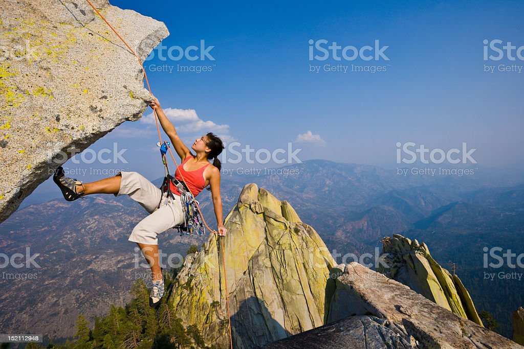 Female rock climber rappelling. stock photo