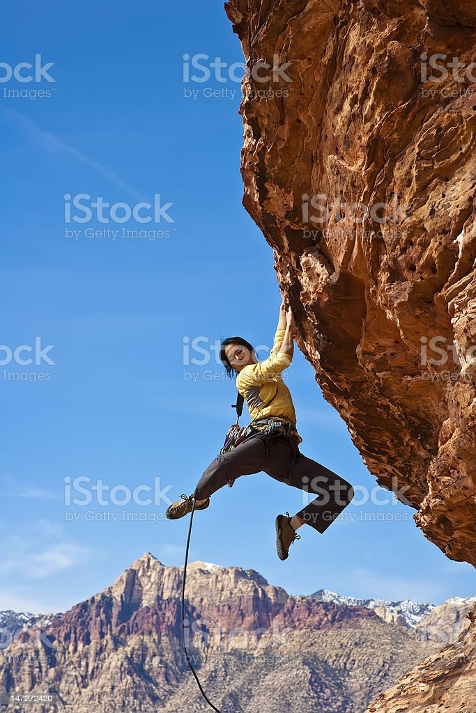 Female rock climber reaching for the summit. royalty-free stock photo