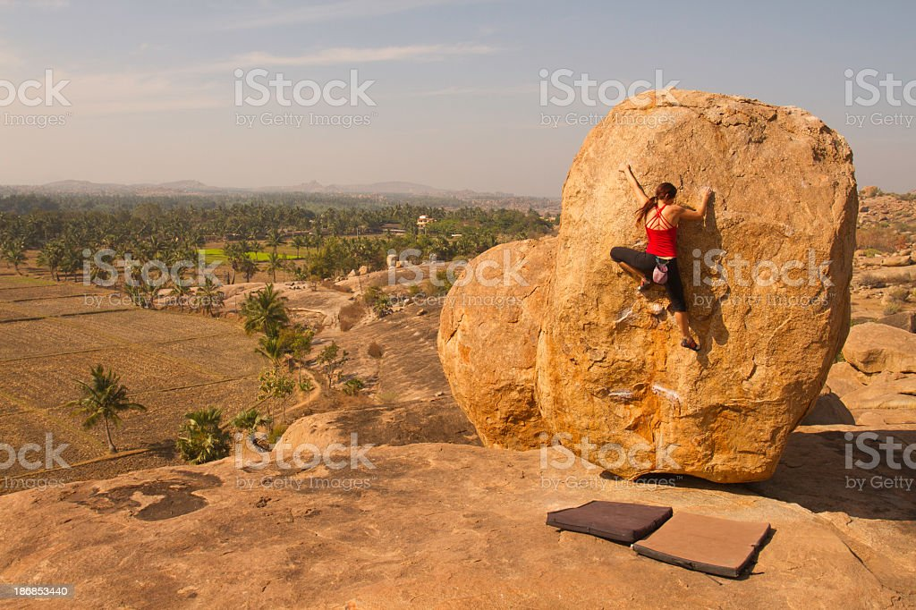 Female rock climber scaling Boulder on top of mountain stock photo