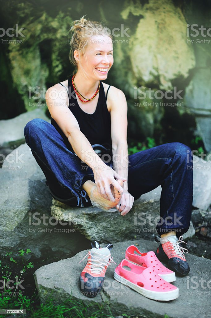 Female rock climber sitting on a stone stock photo