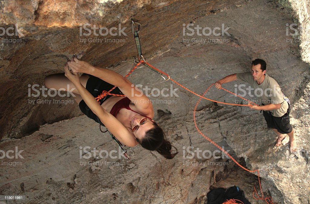 Female Rockclimber and male belayer stock photo