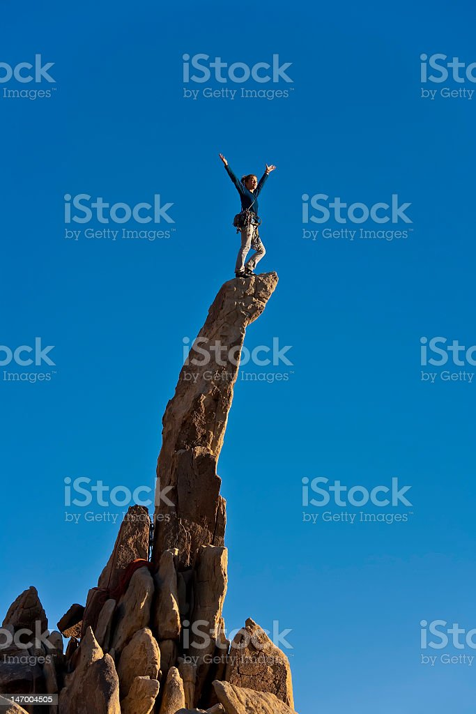 Female rockclimbing at the summit of the rocks royalty-free stock photo