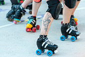 Madrid, Spain - June 20, 2015: Detail of the legs and roller skates of a group of young roller derby girls compete for the position during an exhibition show in La Cebada in Madrid.