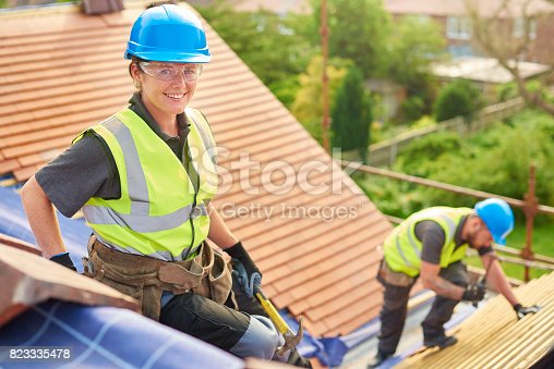 823328086istockphoto female roofer on installation 823335478
