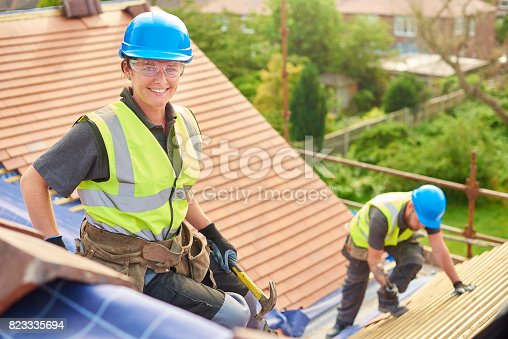 istock female roofer replacing roof tiles 823335694