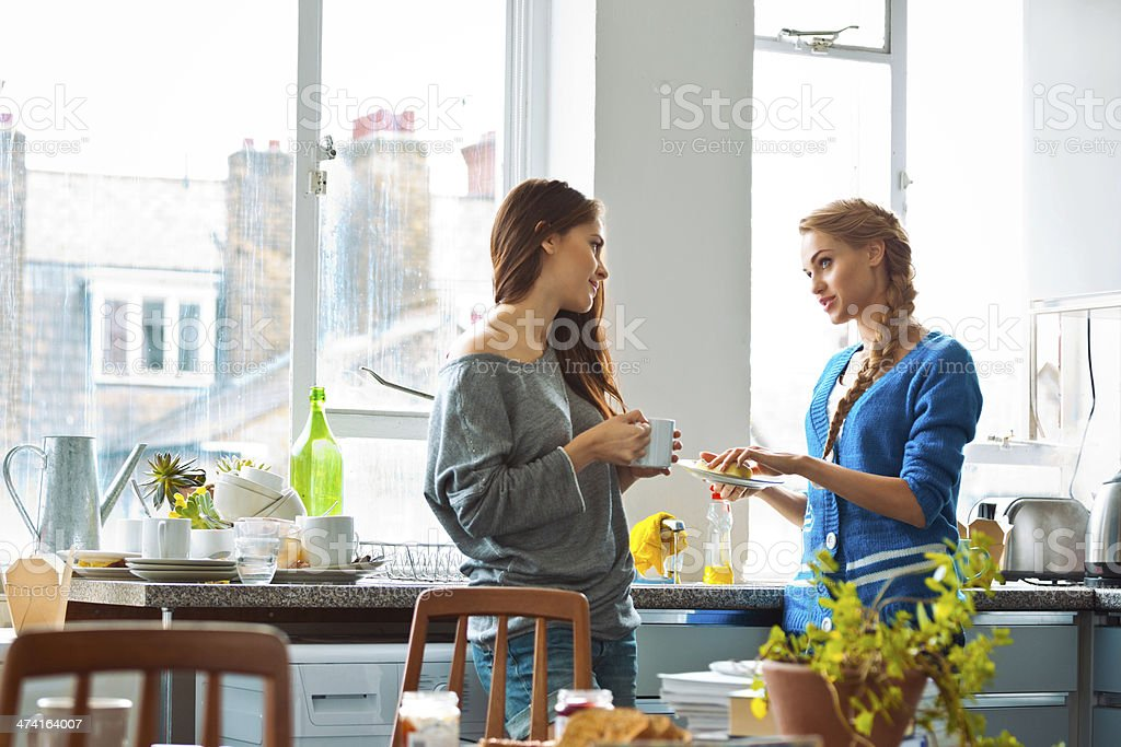 Female roommates Two female roommates talking in the kitchen after breakfast. 20-24 Years Stock Photo