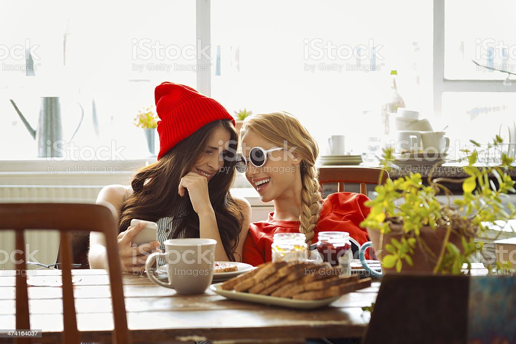 Female roommates Two cheerful friends sitting at the kitchen table and talking over the breakfast. Brunette holding the smart phone in hand. 20-24 Years Stock Photo