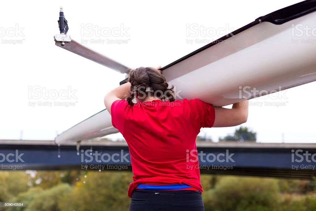 Female rower carrying her scull boat stock photo