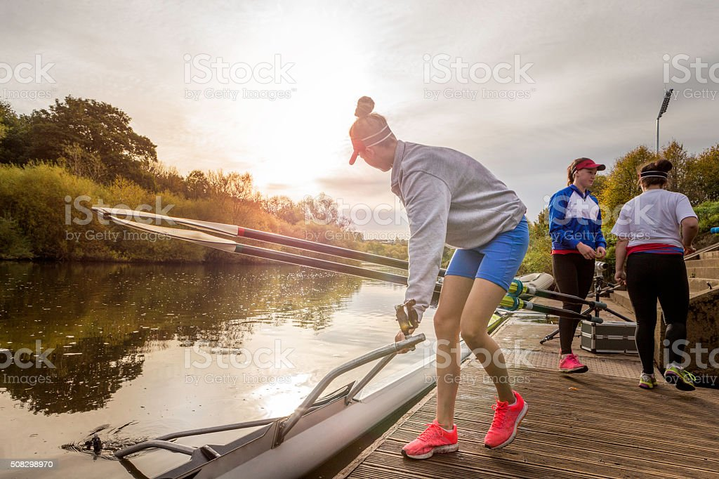 Female rower putting her boat in the water stock photo